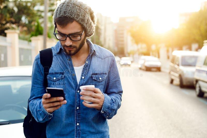 Modern ung man med mobiltelefonen i gatan arkivfoto