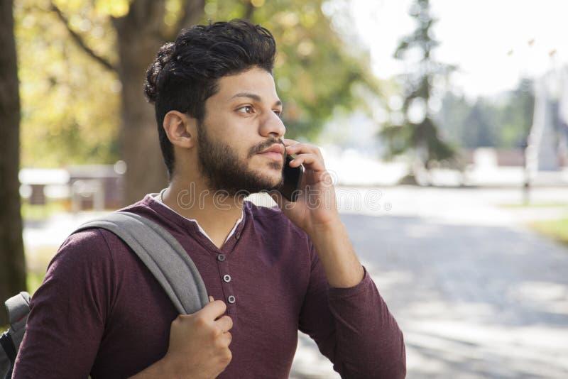 Modern ung man med mobiltelefonen i gatan Utomhus- portra royaltyfri bild