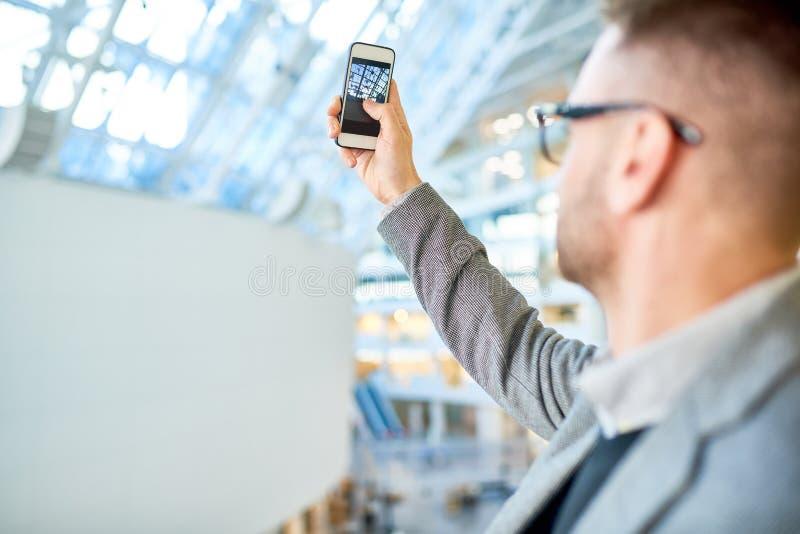 Modern ung man som tar det Smartphone fotoet royaltyfri fotografi