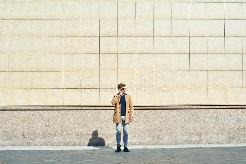 Modern ung man som utomhus talar vid telefonen fotografering för bildbyråer