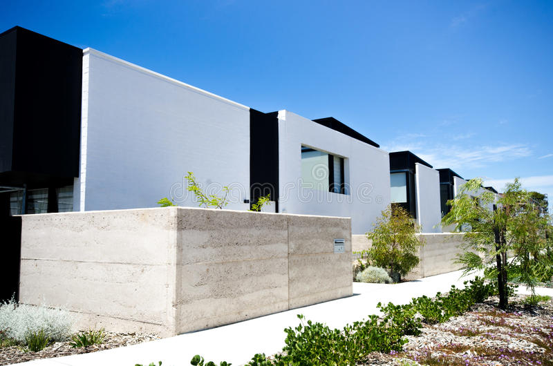 Modern units geometric contrast with sky. Modern units entryways with native plants stock photos