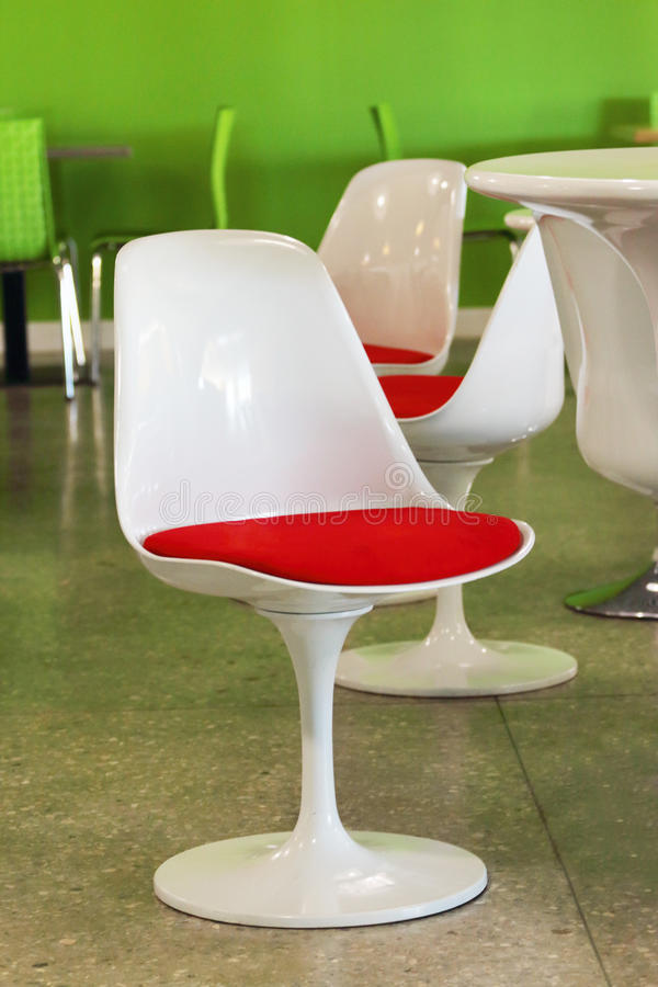 Modern unusual white plastic chairs in empty cafe royalty free stock images