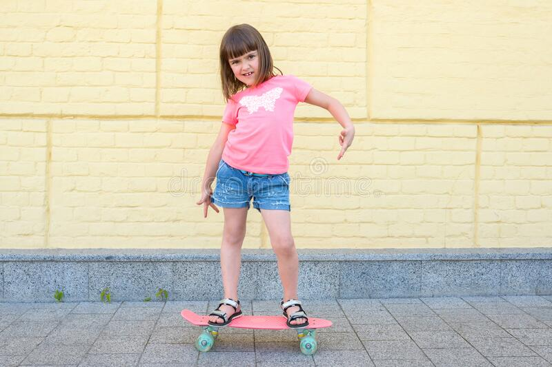 Modern urban hipster girl with a skateboard has fun outdoors. Sport, fitness, lifestyle.  stock photo