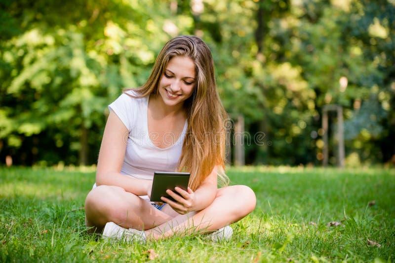 Modern värld - tonårig flicka med minnestavlan arkivbilder