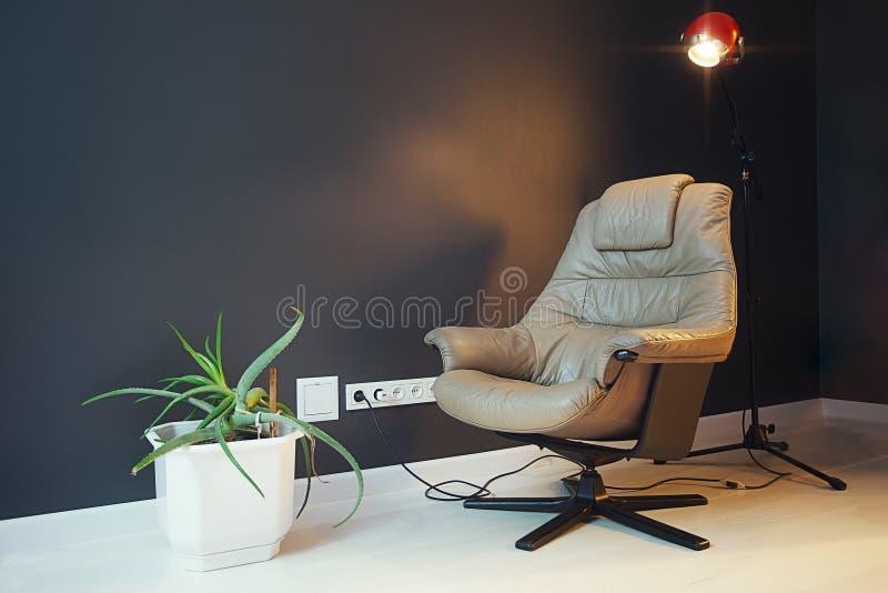 Modern vardagsrum med den beigea läderfåtöljen och svartväggen royaltyfri bild