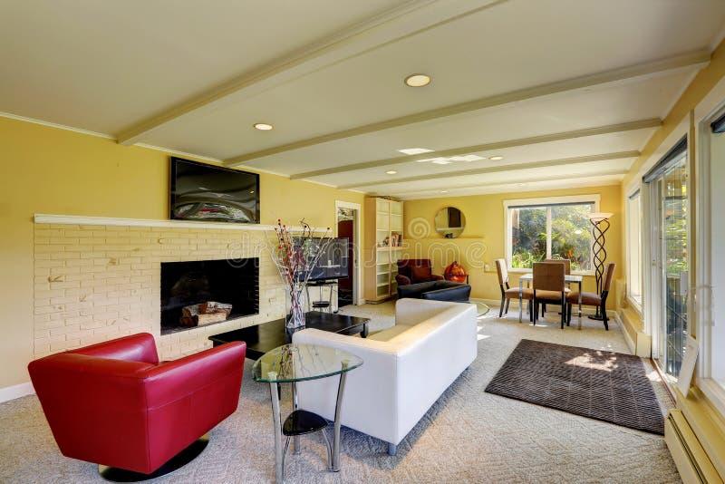 Modern vardagsrum med vita och röda soffor royaltyfri bild