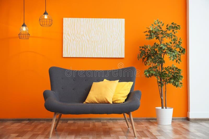 Modern vardagsruminre med den bekväma gråa soffan fotografering för bildbyråer