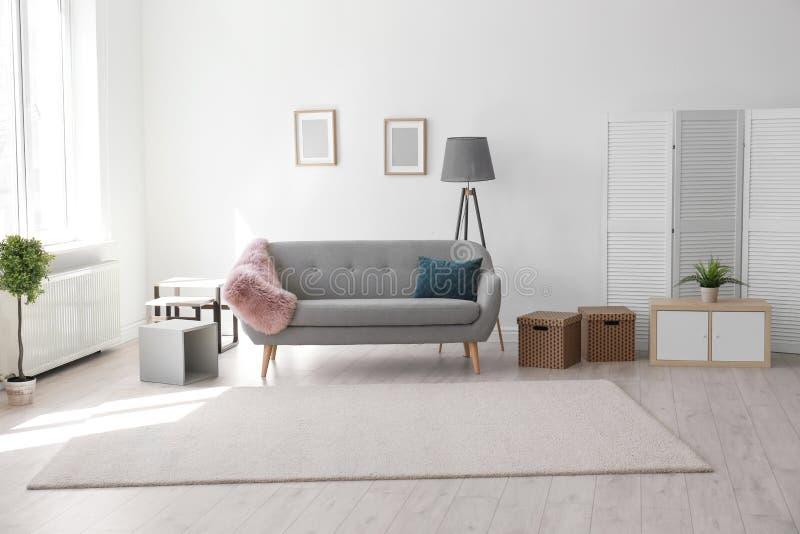 Modern vardagsruminre med den bekväma soffan arkivfoto