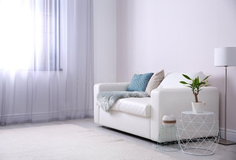 Modern vardagsruminre med den bekväma soffan arkivbild