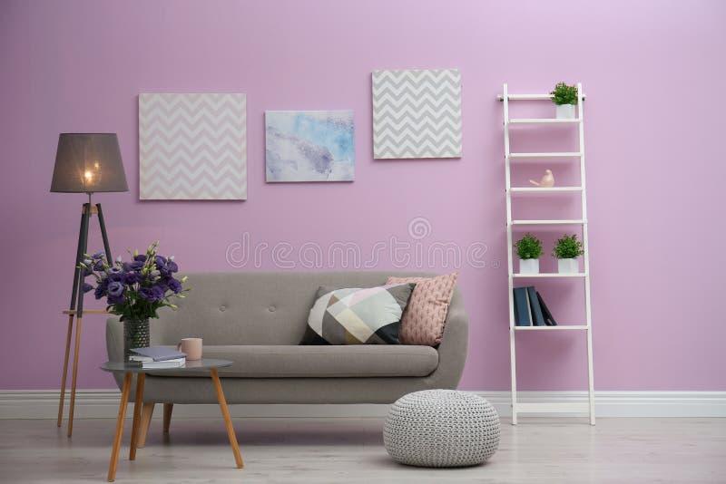 Modern vardagsruminre med den near färgväggen för bekväm soffa royaltyfri fotografi