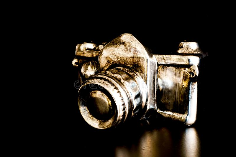 A modern version of a camera in silver and gold. With black background stock photos