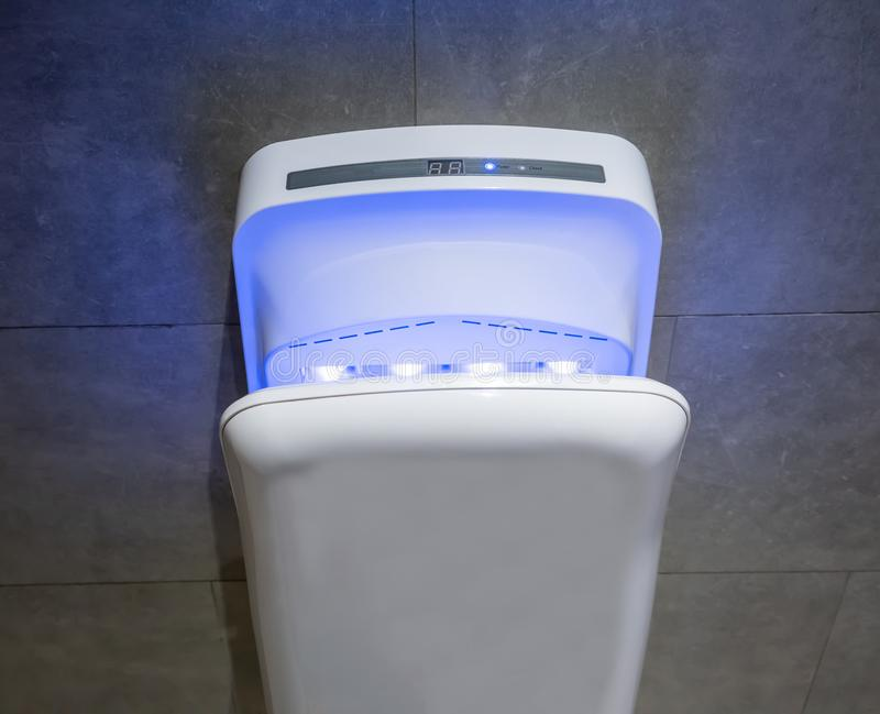 Modern vertical hand dryer in public restroom royalty free stock image