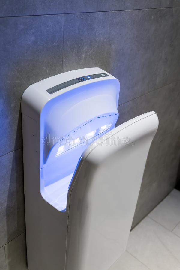 Modern vertical hand dryer in public restroom stock photography