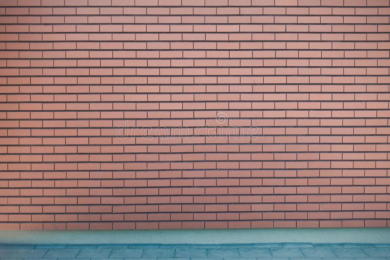 Modern vibrant red brick wall and pavement as a background image stock photo