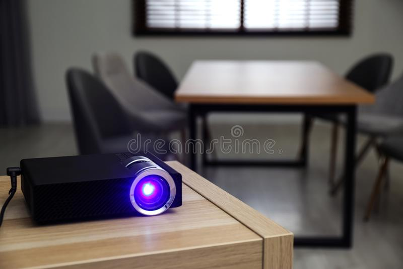 Modern video projector on table in conference room. Space for text. Modern video projector on wooden table in conference room. Space for text royalty free stock image