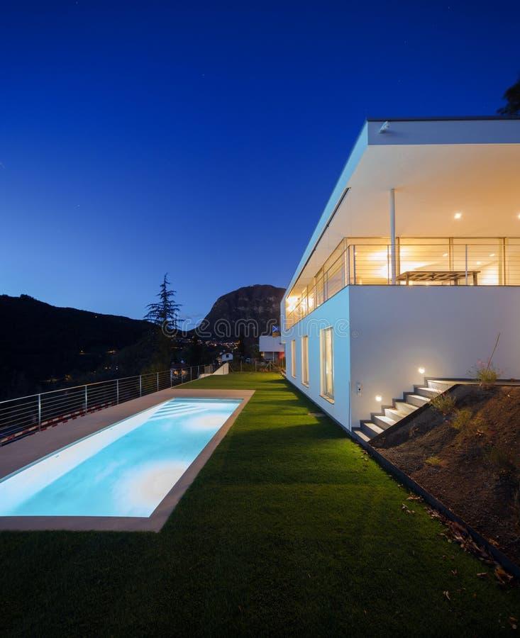 Modern villa, exterior in the night, lights on stock image