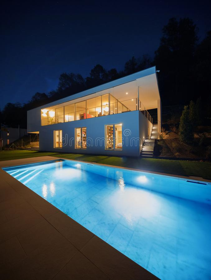 Modern villa, exterior in the night, lights on stock photography