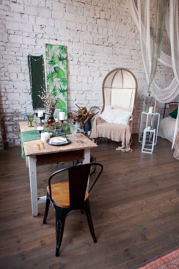 Modern vindvardagsrum med det höga taket, soffa, tom vit tegelstenvägg, wood golv, designtillbehör som äter middag tabellen arkivfoto