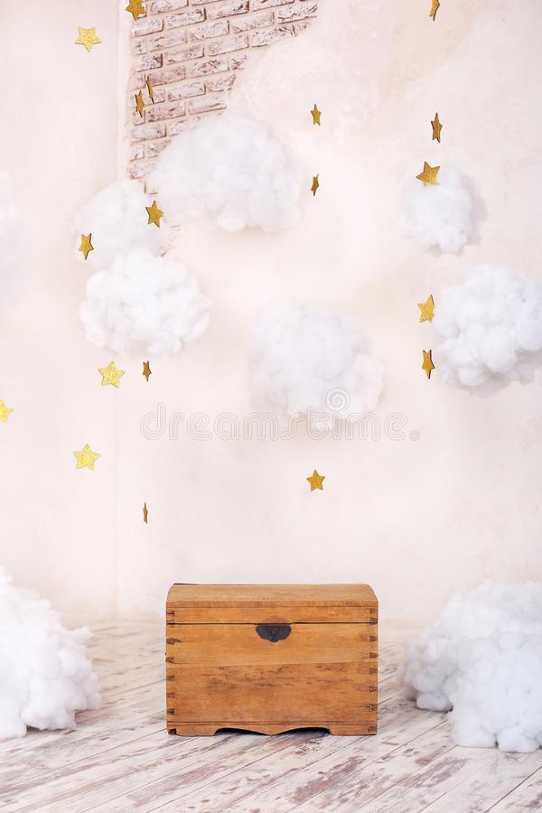 Modern vintage interior of children`s room with an old wooden chest on the background of a textured wall with clouds. Children`s p stock photo