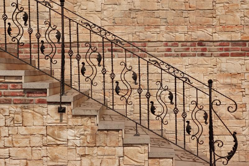 Modern Vintage Style Stone Staircase With Wrought Iron Ornate H. Modern Vintage Style Straight Stone Staircase With Black Wrought Iron Ornate Handrail Near Tiled royalty free stock photo