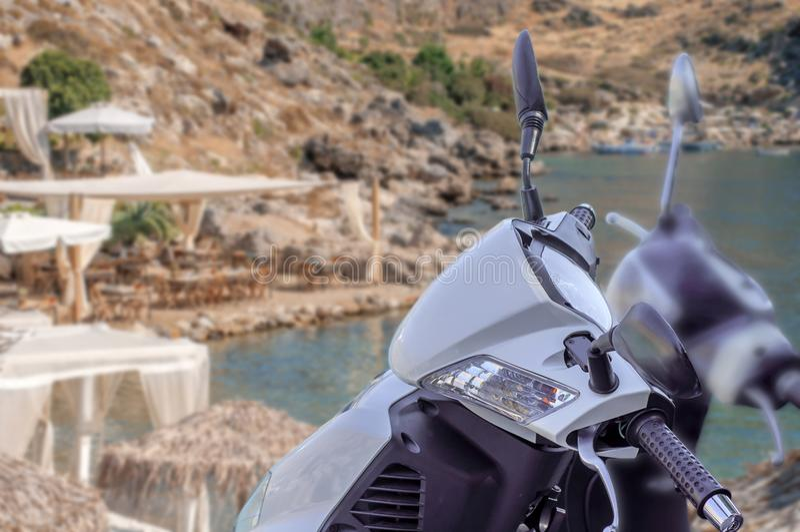 Modern vit skinande motorcykel för trans. med stranden arkivbilder