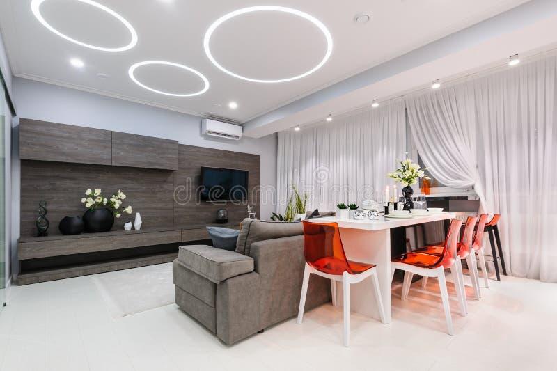 Modern vit vardagsrum med att äta middag tabellen royaltyfria bilder