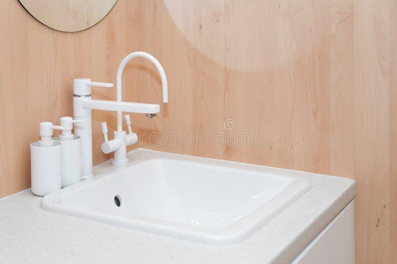 Modern vit vattenkran och keramisk vask Inre detaljer för Minimalist badrum arkivbilder