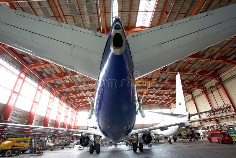 Modern vliegtuig in de hangaar stock foto