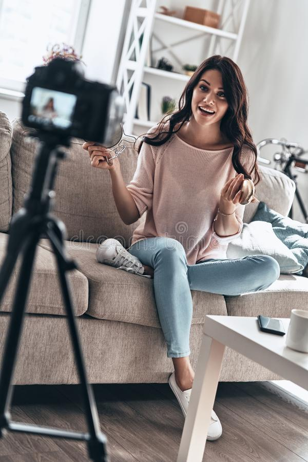 Modern vlogger. Beautiful young woman holding beauty products and smiling while making social media video royalty free stock image