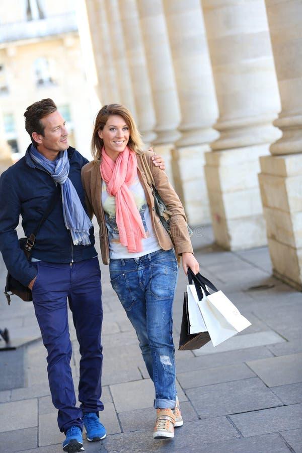 Modern vrolijk paar die op middelbare leeftijd in stad lopen stock foto