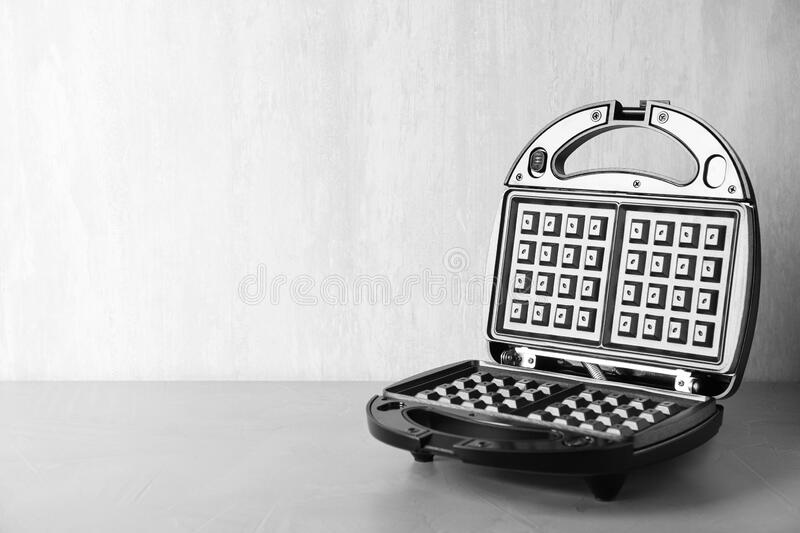 Modern waffle iron on grey stone table. Space for text. Modern waffle iron on grey stone table stock images