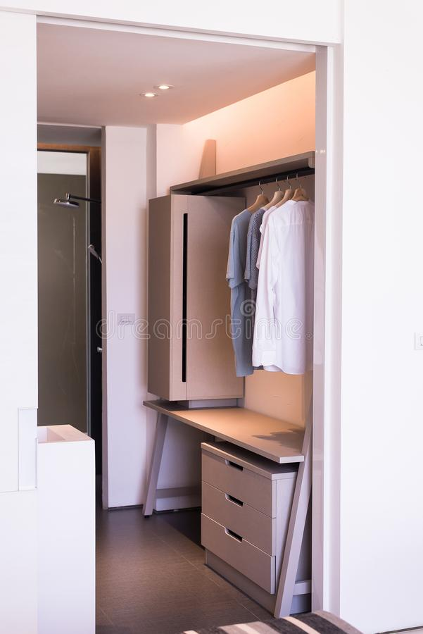 Modern walk in closets design interior with clothes hanging on rail. In modern room royalty free stock photos