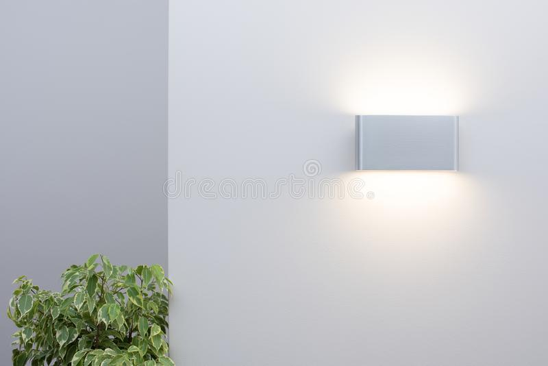 Modern wall lamp on a light wall. Free space and decor. In the interior royalty free stock photography