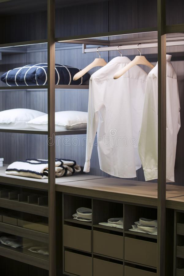 A modern wardrobe room with lighting, with examples of shelves for clothes in the apartment.  stock photography