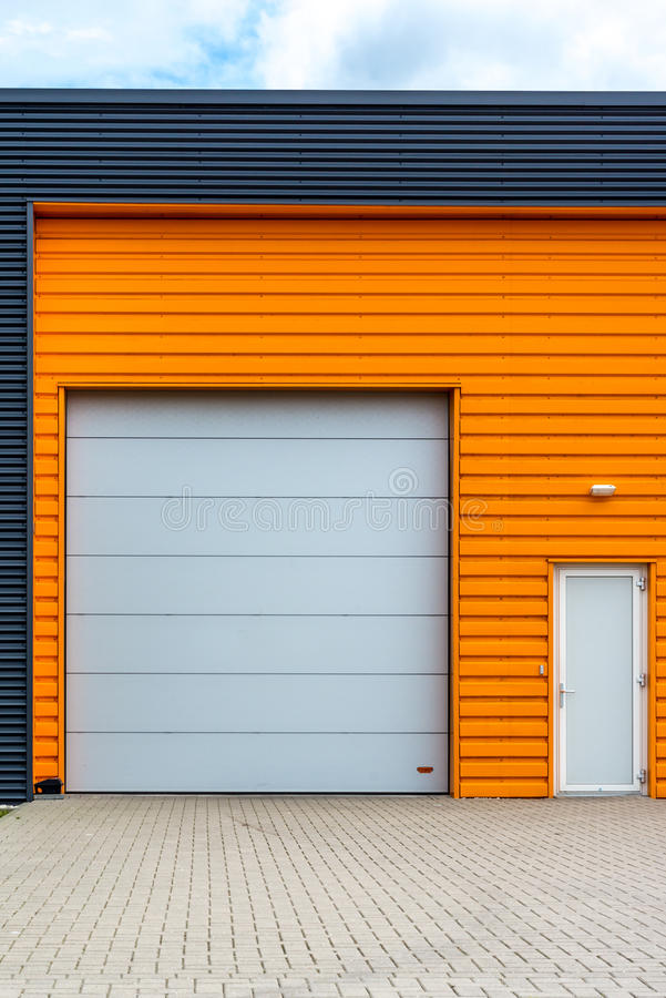 Modern warehouse entrance with orange front royalty free stock images