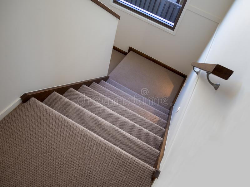 Modern carpeted staircase with night lighting and wooden handrail stock photos