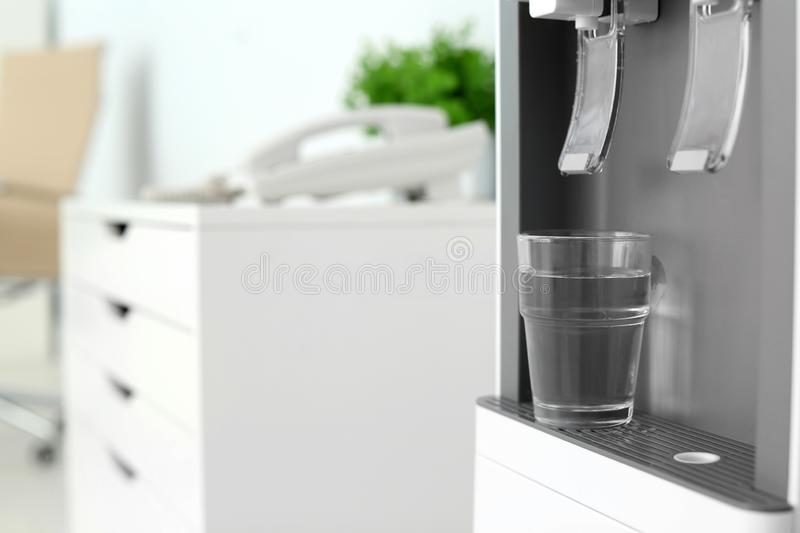 Modern water cooler with glass in office, closeup. Space for text stock images