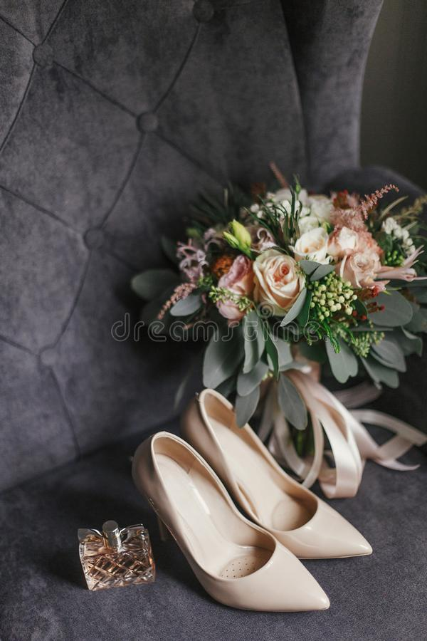 Modern wedding bouquet, beige shoes and perfume bottle on stylish grey sofa. Contemporary composition of stylish bridal. Accessories for wedding day stock photo