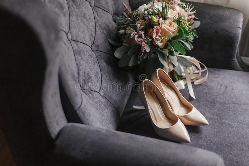Modern wedding bouquet, beige shoes and perfume bottle on stylish grey sofa. Contemporary composition of stylish bridal. Accessories for wedding day stock photography
