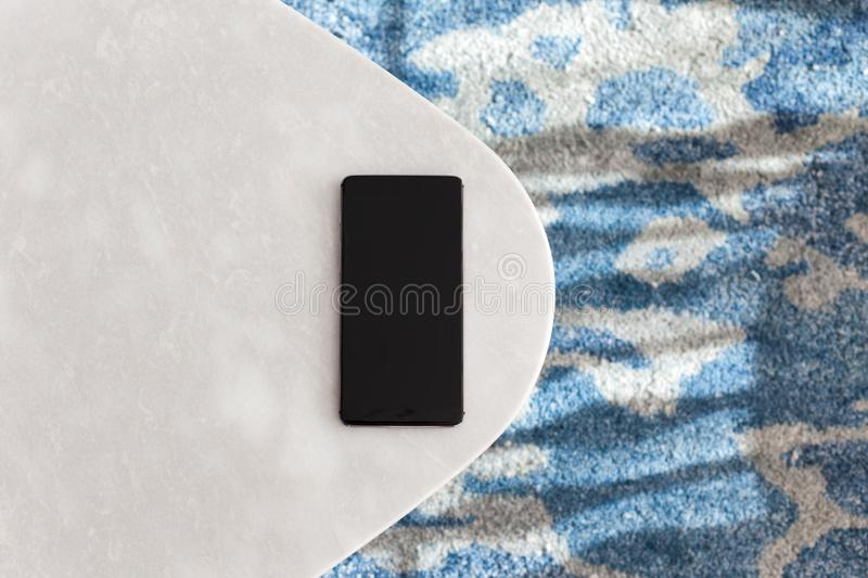 Modern white table made of artificial stone. Modern whiteе table made of artificial stone stands on a carpet with fine nap, a top view. The mobile phone lies stock images