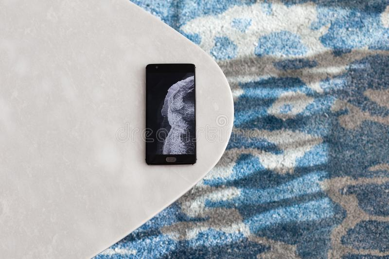 Modern whiteе table made of artificial stone stands on a carpet with fine nap, a top view. The mobile phone lies on a new small table royalty free stock photography