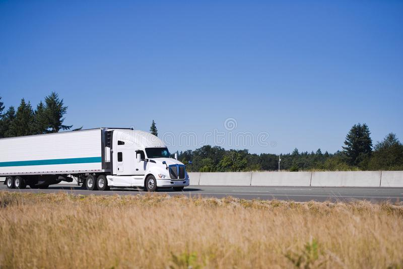 Modern white big rig semi truck with reefer trailer running on h. Modern white big rig semi truck tractor with high cab for comfort truck driver sleeping during stock photos