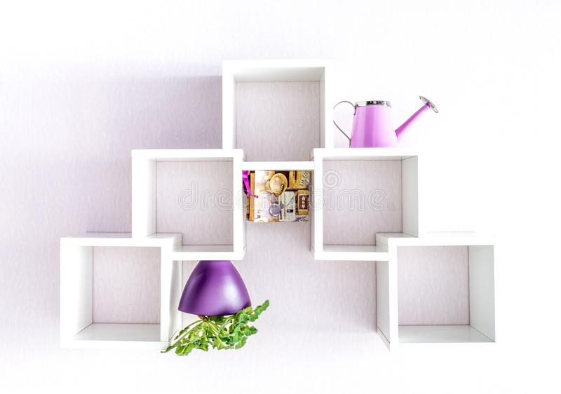 A modern white bookshelf on a white wall with a few things and a flower. Minimalism style. A modern white bookshelf on a white wall with a few things and a royalty free stock images