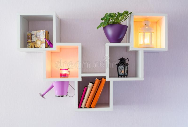 A modern white bookshelf on a white wall with a few things, a flower, and burning candles. Minimalism style.  stock photo