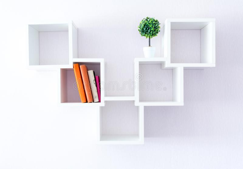 A modern white bookshelf on a white wall with a few things and a flower. Minimalism style. royalty free stock image
