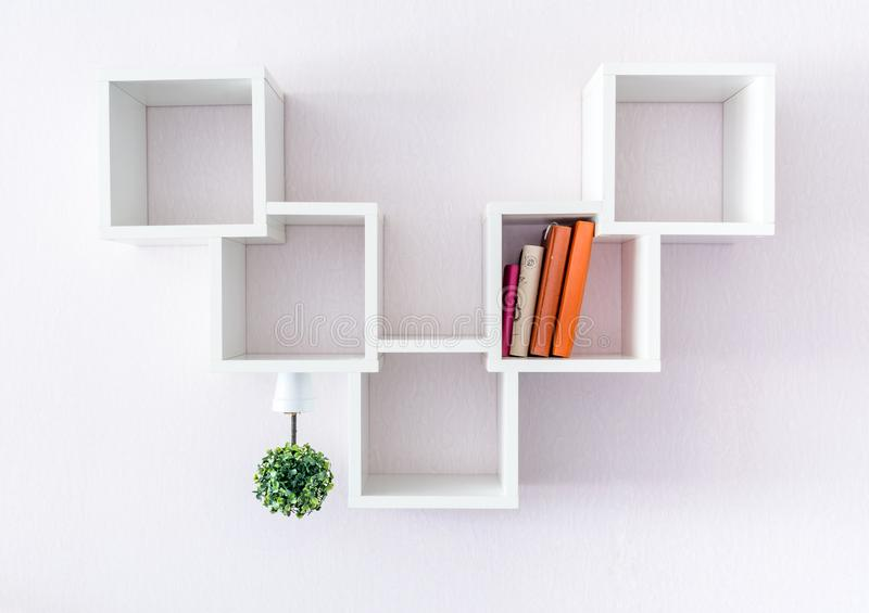 A modern white bookshelf on a white wall with a few things and a flower. Minimalism style. A modern white bookshelf on a white wall with a few things and a royalty free stock photo