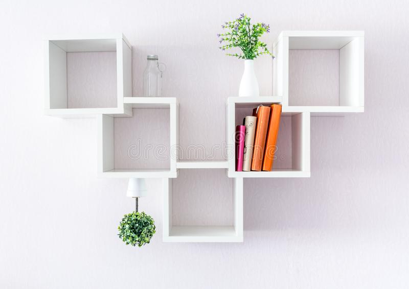 A modern white bookshelf on a white wall with a few things and a flower. Minimalism style. A modern white bookshelf on a white wall with a few things and a stock images