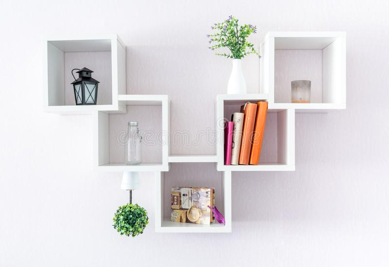 A modern white bookshelf on a white wall with a few things and a flower. Minimalism style.  stock image