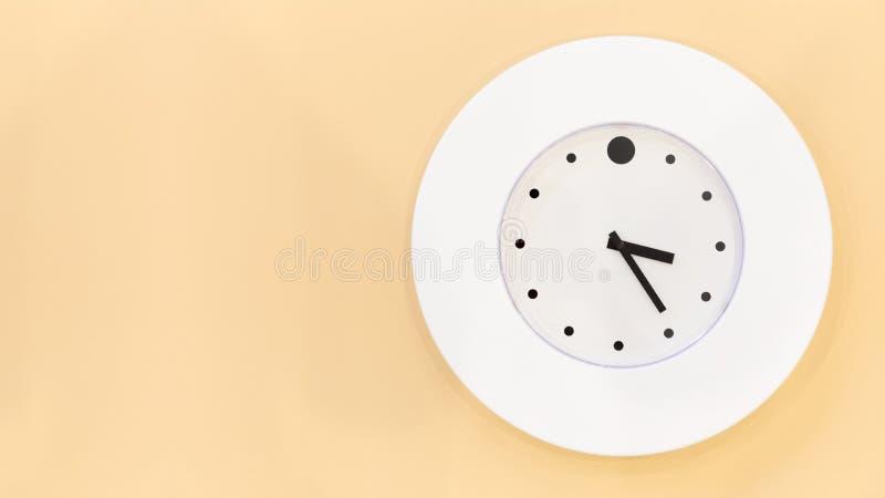 A modern white clock hanging on orange wall stock photo