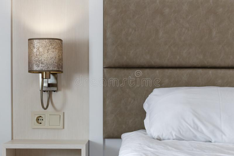 Modern white color tone bedroom, white pillow and bed linen, modern lamp turned on stock image